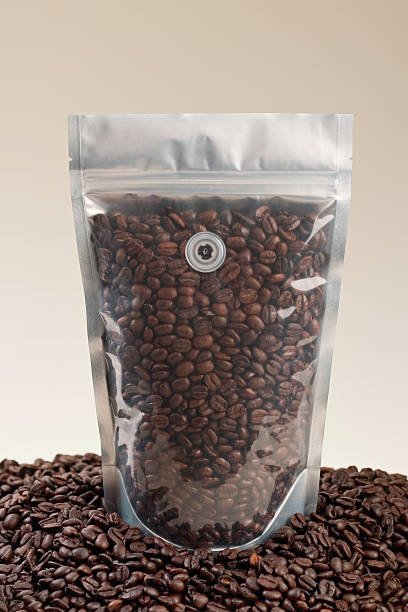 A designer friendly clear coffee pouch surrounded by delicious roast coffee beans.  Ready for your spiffy label and label design!